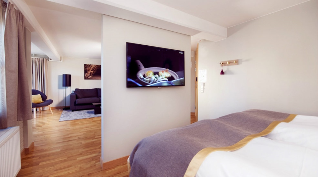 Dubbelsäng och TV i Deluxerum på Clarion Collection Hotel Bryggeparken